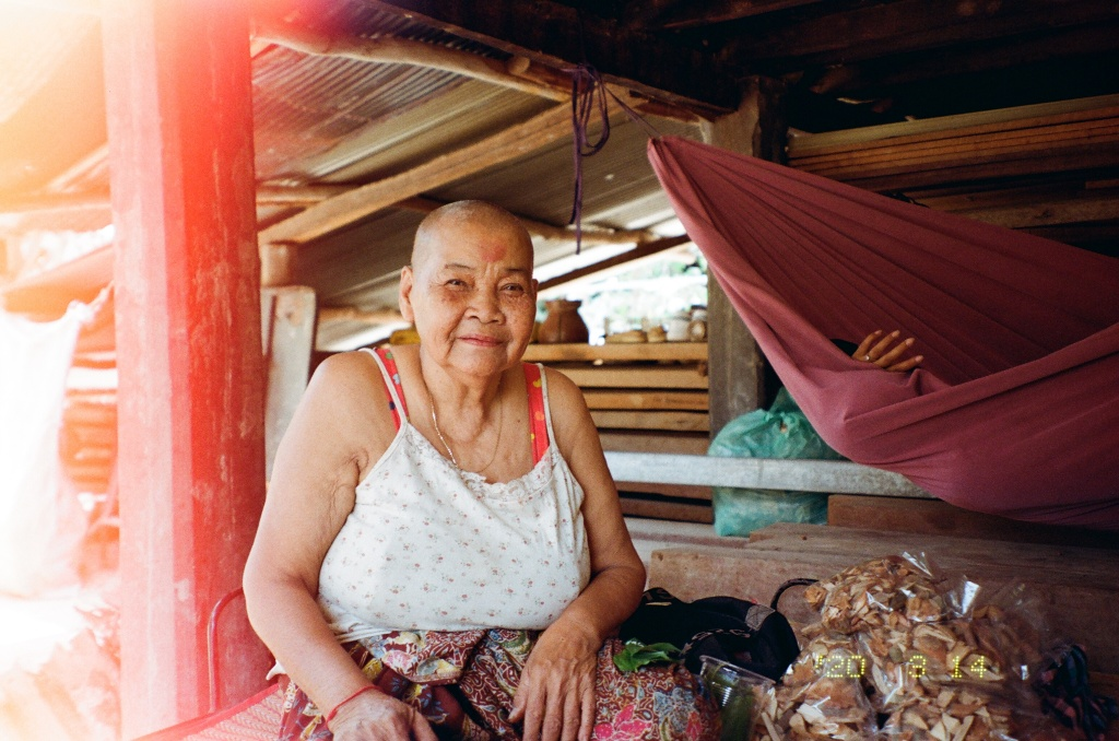 An elderly Cambodian woman with a shaved head sits on a raised dark wood platform, next to a pile of plastic packages filled with Traditional Khmer medicine woody plant materials. She is looking into the camera and smiling slightly. She wears a white sleeveless shirt which is dotted with light red floral patterning, a sarong which is also floral and multicolored in design, a light golden chain around her neck, and a red thread bracelet on her left wrist. In the background is as a red hammock to her right side, where the hand of her granddaughter is poking out; to her left are a series of wooden shelves covered in earthy pots and are covered by a tin roof.